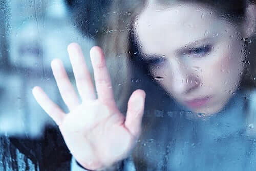 trist kvinde bag regnfyldt vindue