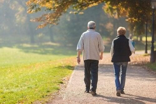 Ældre ægtepar går en tur sammen i solskinsvejr