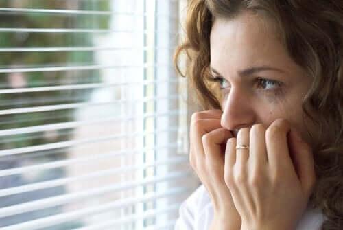 angst kvinde, der kigger ud af et vindue