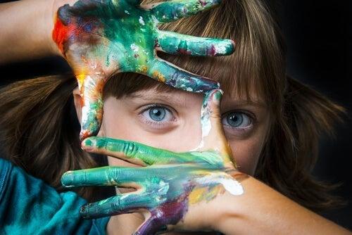 barn med maling på hænderne