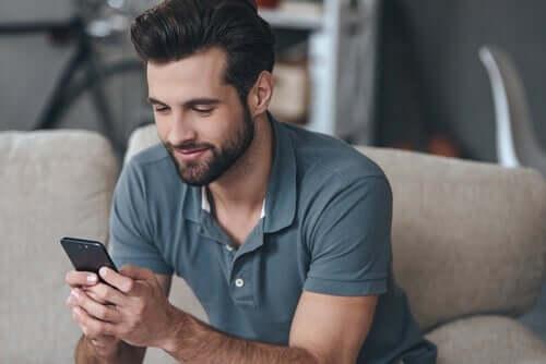glad mand med sin mobiltelefon