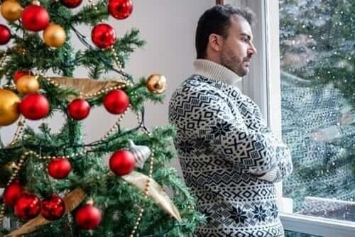 Fortvivlet mand ved juletræ har problemer med at være selvsikker i familien i juledagene