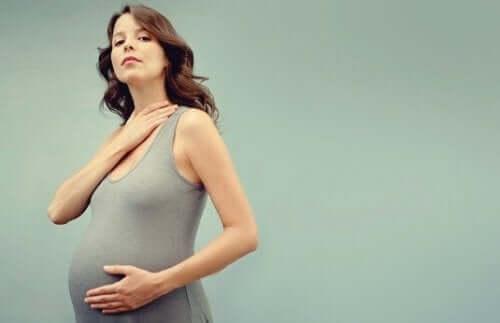 gravid kvinde, der holder på mave og hals