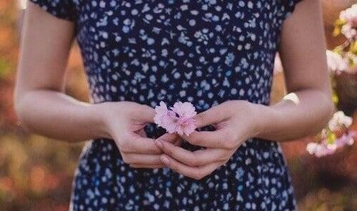 Kvinde står med blomst i hånden