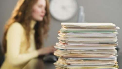 kvinde, der får adrenalinsus ved at udskyde ting, sidder med en masse papirer