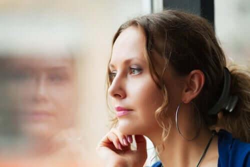 kvinde, der kigger betænksomt ud af vindue