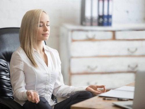 kvinde, der mediterer på kontor