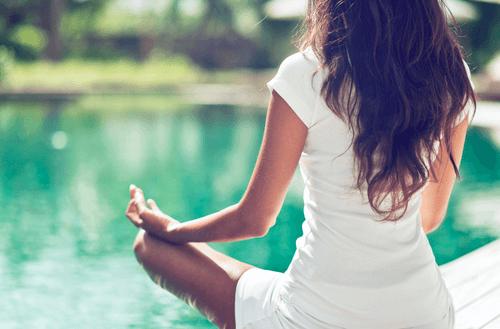kvinde, der mediterer ved sø