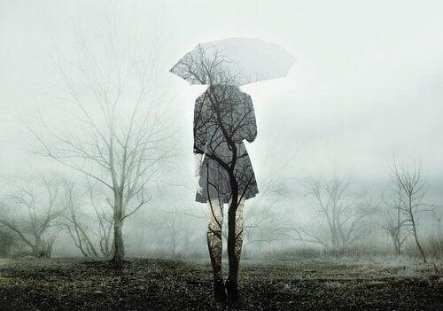 Kvinde står i gråvejr med paraply