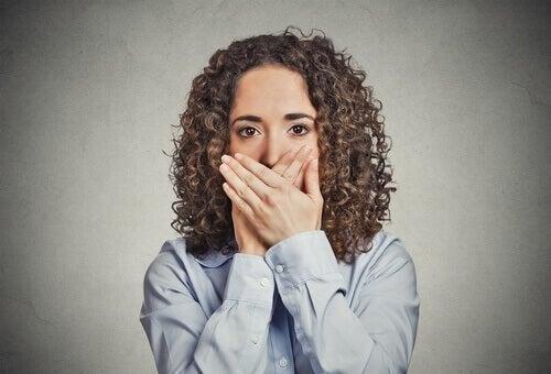 Kvinde holder sig for munden