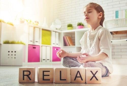 """Pige mediterer ved siden af træklodser, der danner ordet """"relax"""""""