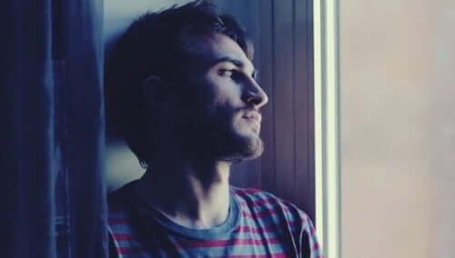 mand, der kigger ud af vindue