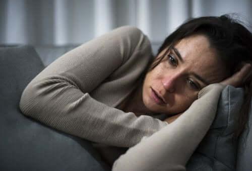 Kvinde med kognitivt opmærksomhedssyndrom græder på sofa
