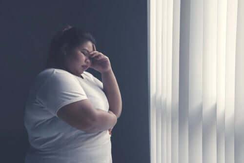 Overvægtig kvinde ved vindue