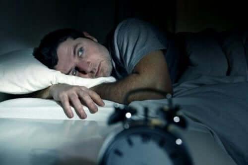 mand ligger søvnløs i sengen som resultat af at gå i seng med vrede
