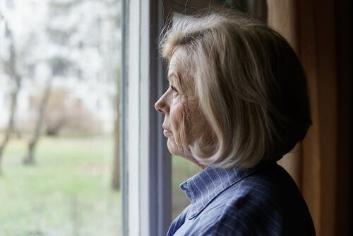 Ældre kvinde kigger ud af vinduet