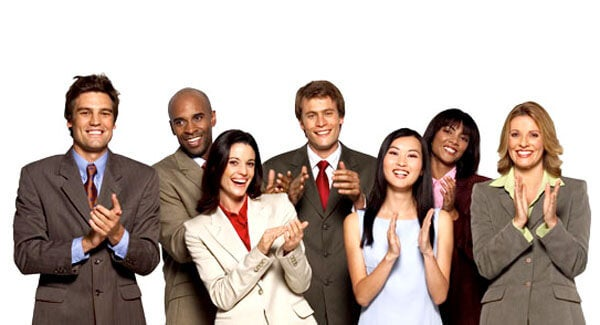 Personer i pænt arbejdstøj står og klapper som eksempel på at få en kompliment
