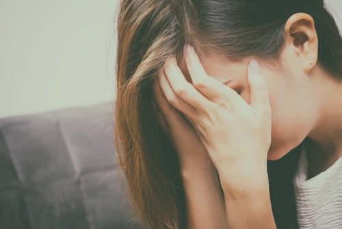 Kvinde, der skjuler ansigt bag hænder, føler delt ulykkelighed