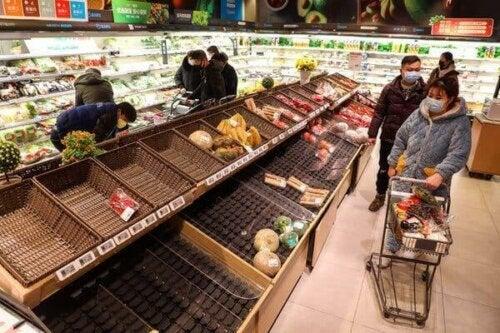 Folk handler i supermarked med tomme hylder grundet coronavirus hamstring