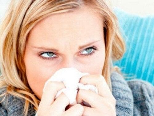 Forkølet kvinde pudser næse