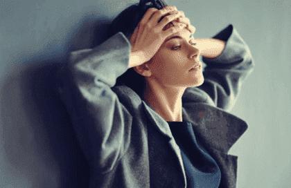 Frustreret kvinde, der læner sig op ad væg