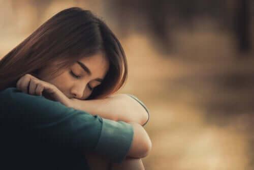 Kvinde med lukkede øjne hviler hoved på arme