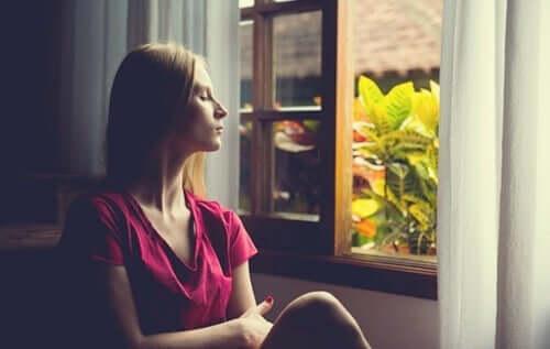 kvinde ser ud af vindue for at undgå altid at bruge de samme løsninger på hendes problemer