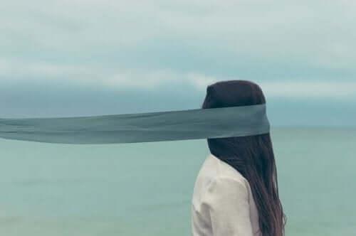 Kvinde med bind for øjnene for at se mere end det, der er