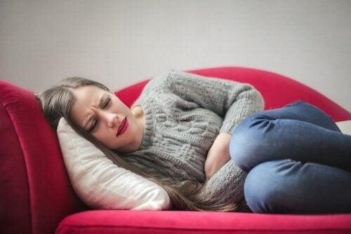 Kvinde ligger på sofaen med kraftige smerter