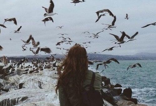 Kvinde ser på fugle over hav