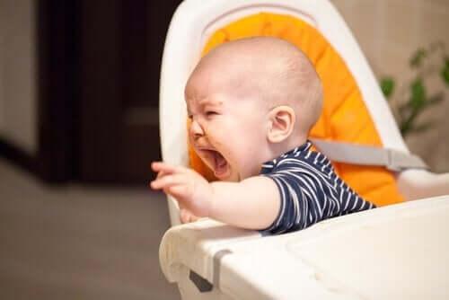 et barn skriger i højstol