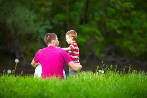En dreng med sin far på en plæne