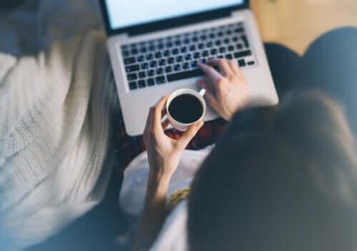 Person, der arbejder på computer og drikker kaffe