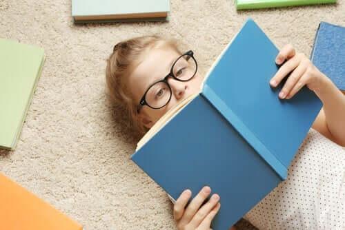 Pige på gulv læser bog