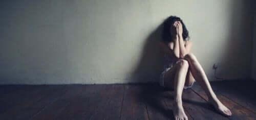 fortvivlet kvinde sidder på gulvet