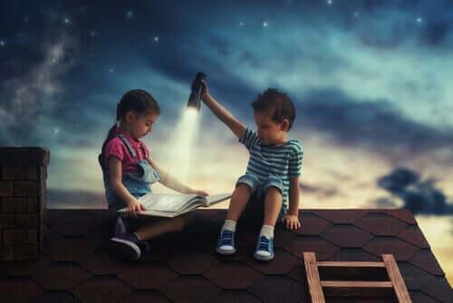 To børn læser sammen på tag om natten