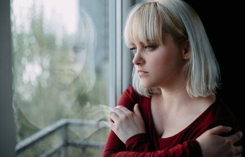 trist kvinde, der kigger ud af vindue