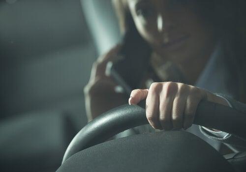 Kvinde taler i mobil bag rattet