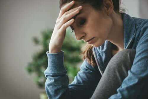 Nedtrykt kvinde tager sig til hoved