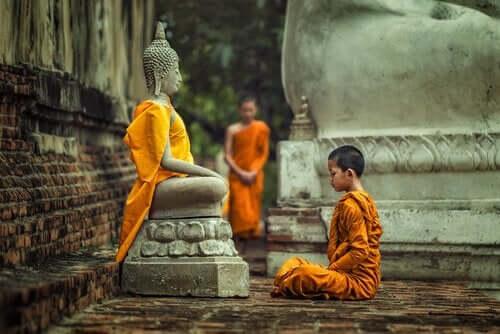 Dreng, der sidder foran statue