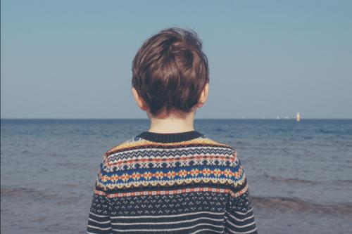 Et sørgende barn, der kigger ud på havet