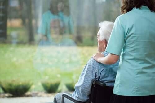 Mand, der ser ud af vindue, oplever demenssygdom