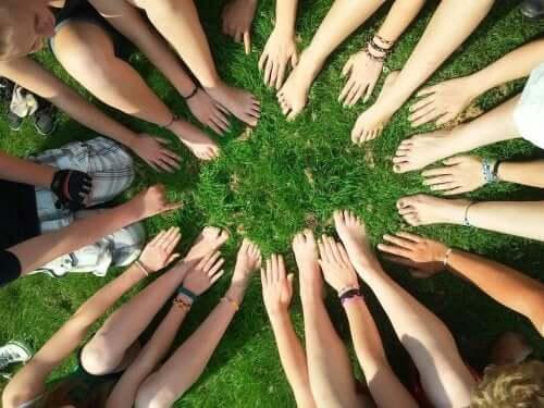 Folk, der sidder i cirkel på græs