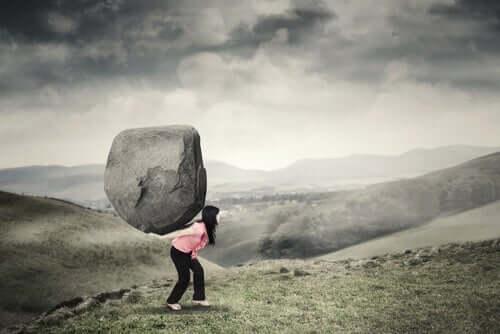 kvinde bærer meget stor sten på ryggen