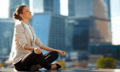 Kvinde mediterer i en storby