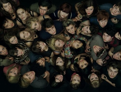 Gruppe af unge folk, der står tæt sammen og kigger op