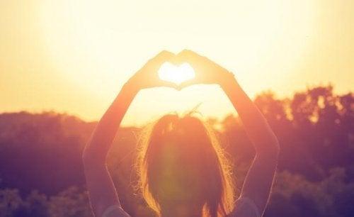 Kvinde danner hjerte med hænder over hoved