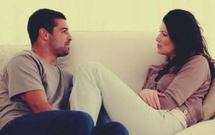 Kommunikationen i et parforhold: Par sidder sammen på sofaen og taler