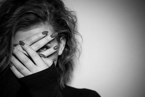 Kvinde, der holder sig for ansigtet