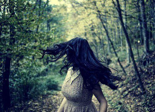 Kvinde, der løber i skov og ser sig tilbage, oplever et adrenalinkick